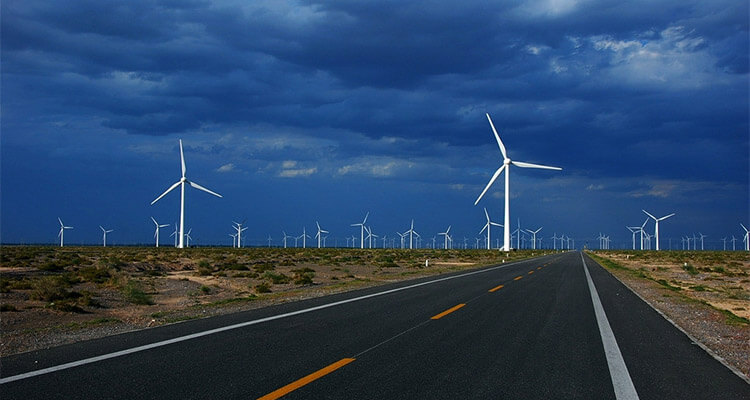 a picture of onshore wind farm next to highway